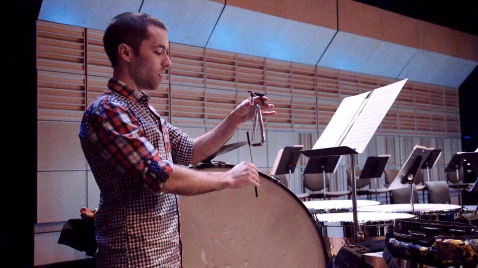 Le percussionniste du Vancouver Island Symphony, Gaël Chabot-Leclerc tenant dans sa main gauche le triangle, petit instrument de percussion.