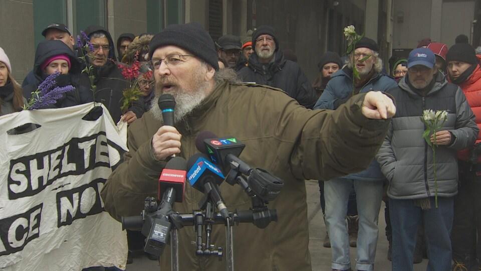 Gaétan Héroux s'exprime depuis la rue, devant plusieurs micros des médias, entouré d'activistes.