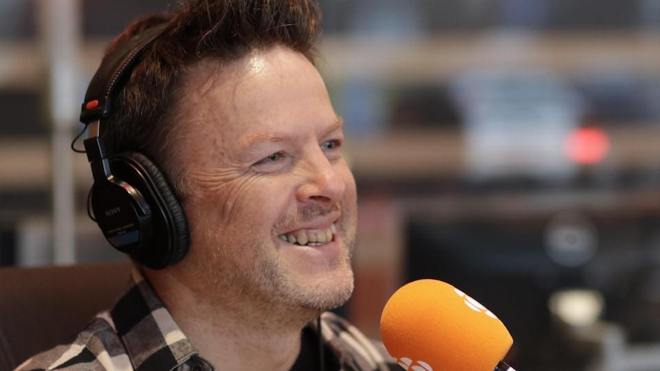 Une homme souriant qui parle au micro.