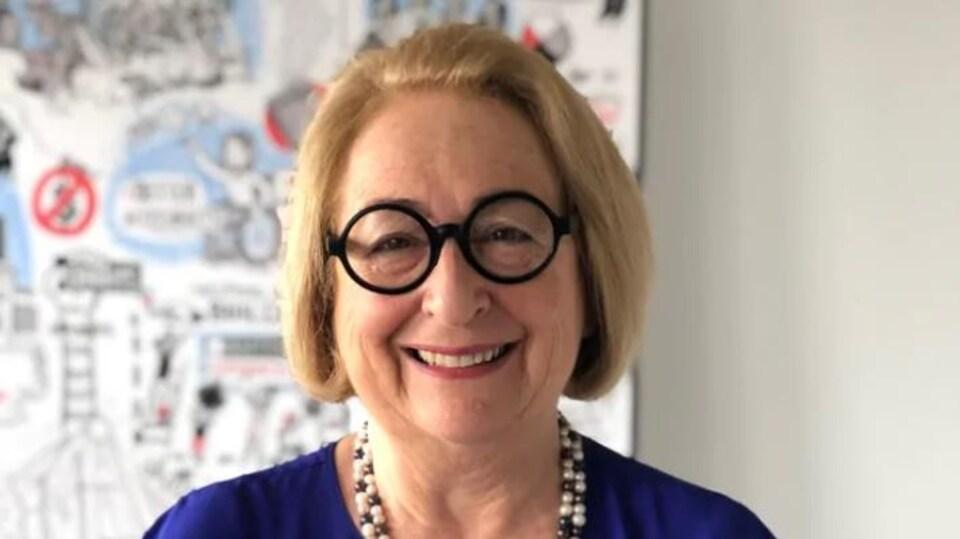 Gail Lord presidente de museum consultancy Lord Cultural Resources porte un chandail bleu marine, des lunettes rondes et noires, un colliers en perles blanches et noires, elle sourit, elle doit avoir une soixantaine d'années, elle a les cheveux blonds en carré court.