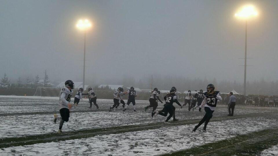 Les joueurs de football sous la neige.