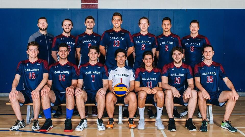 Des joueurs de volleyball posent pour une photo officielle, en deux rangées, dans un gymnase.