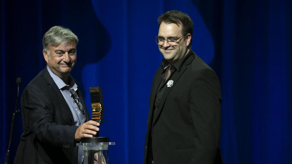Deux hommes en complet sourient à la foule en tenant un trophée.