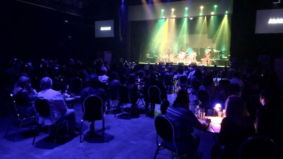 Des gens assis dans une salle regarde un spectacle de musique s ur une estrade.