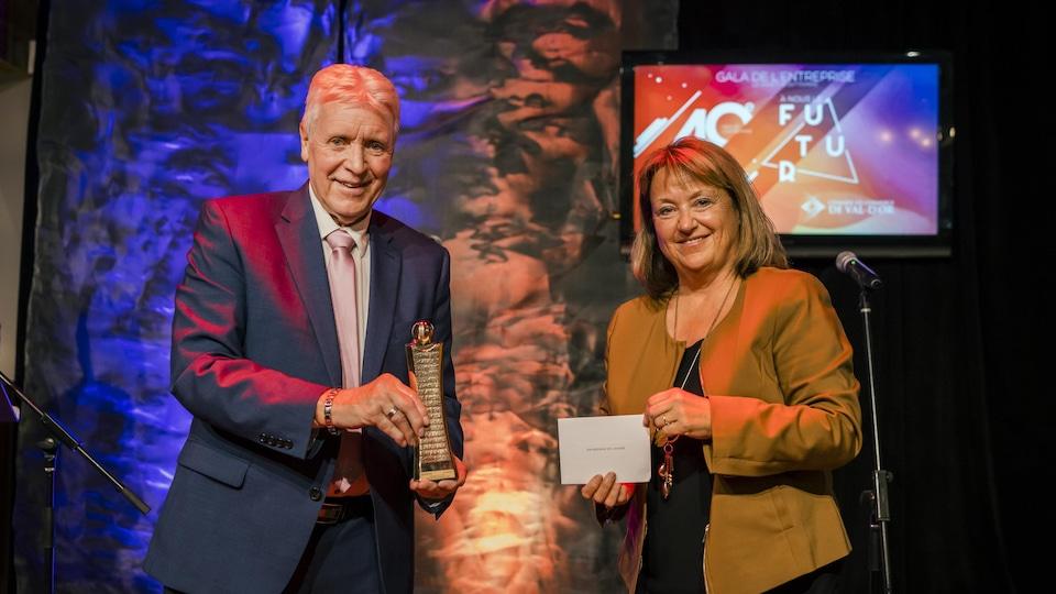 Un homme tient un prix dans ses mains et une femme à ses côtés tient un carton indiquant entreprise de l'année