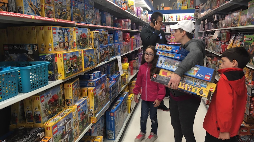 Une mère et ses deux enfants dans une rangée de magasin.