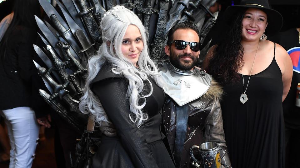 Deux personnes déguisées en personnage de la série sont assis sur un thrône de fer.