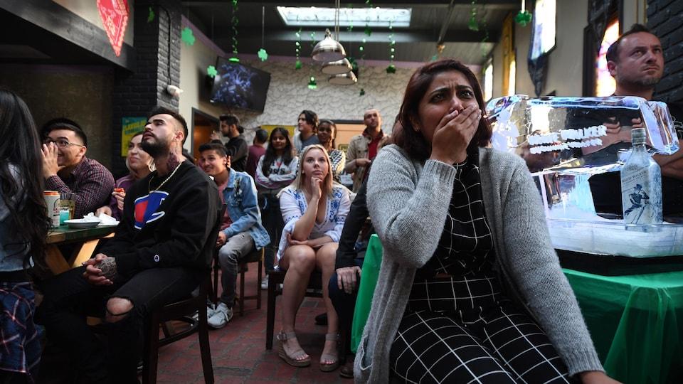 Des personnes regardent la série dans un bar.