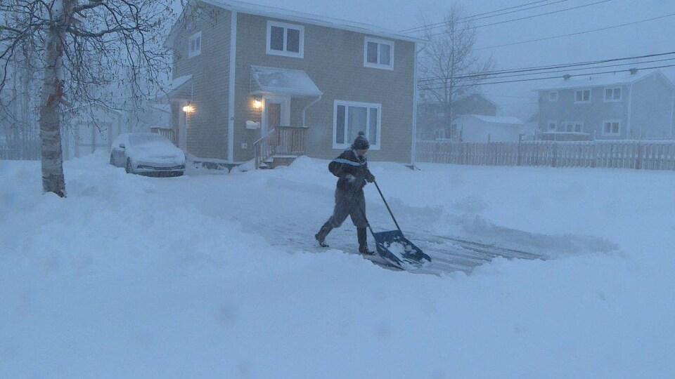 Une femme pousse la neige de sa cour à l'aide d'une grande pelle