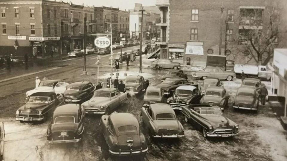 Photo historique montrant des voitures d'époque stationnée devant le garage Esso.