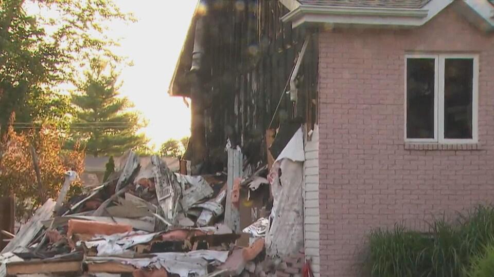 Des débris jonchent le sol près d'une maison à la suite de la destruction d'un garage.