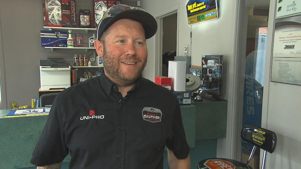 Un homme avec une casquette pose pour la caméra dans une entrée de garage.