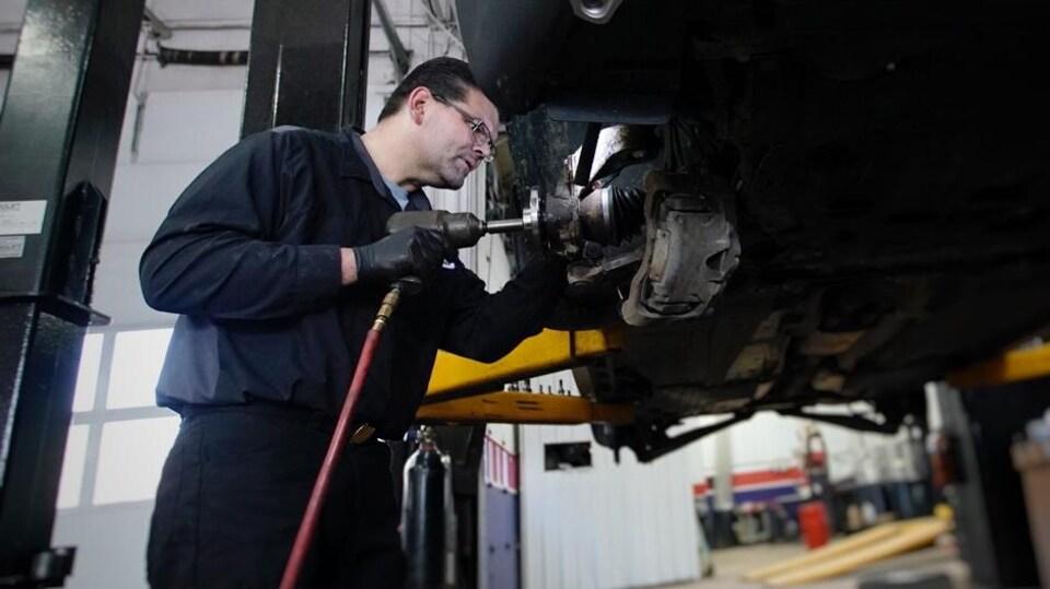 Un garagiste travaille sur une voiture.