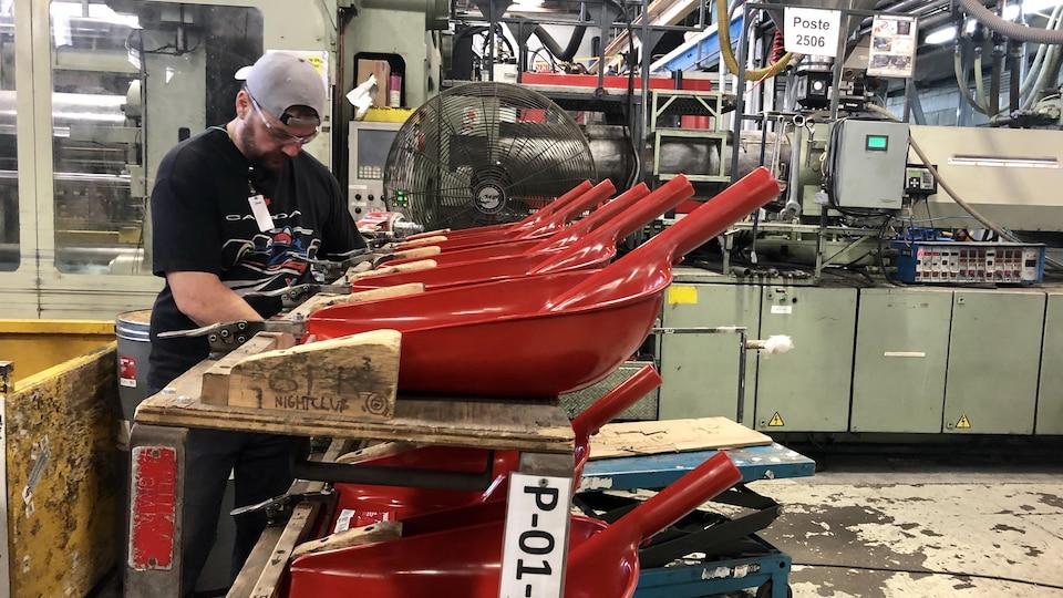 Un homme travaille dans une usine de pelles.