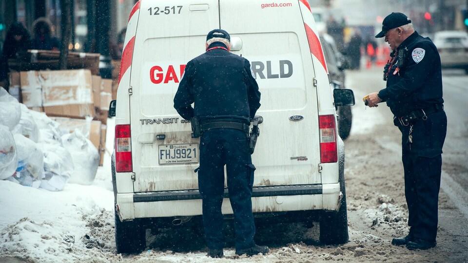 Deux agents travaillent derrière leur camion.
