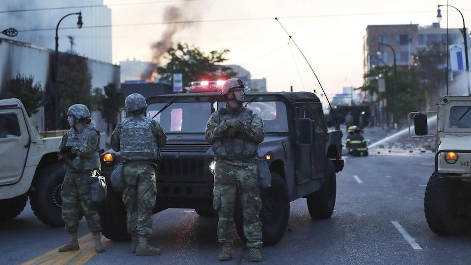 Des soldats se tiennent debout devant un convoi militaire.