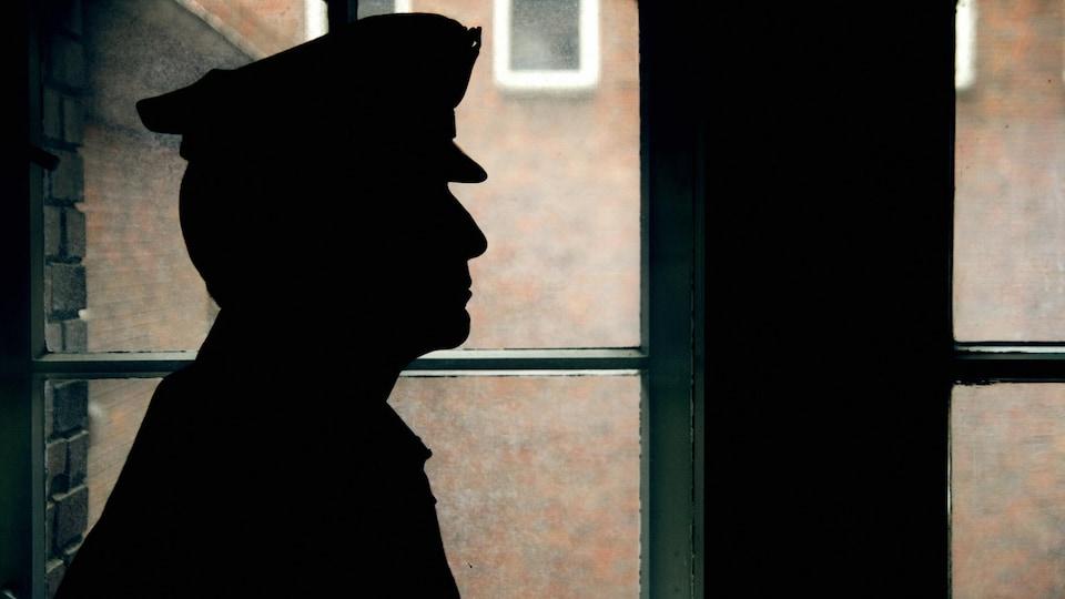 Un gardien de prison, portant une casquette, de profil dans l'ombre.