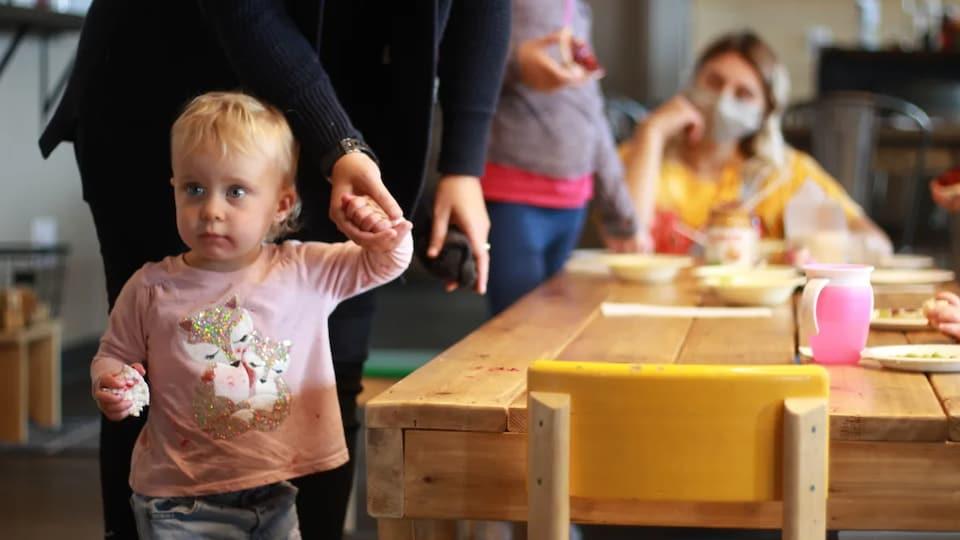 Un enfant tient la main d'un adulte dans une garderie.