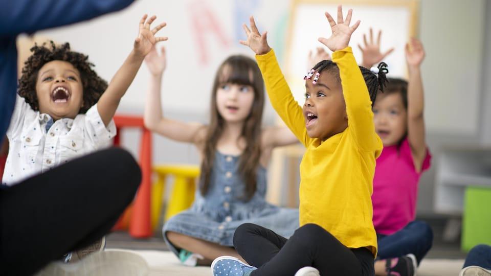Des enfants lèvent les bras en chantant.