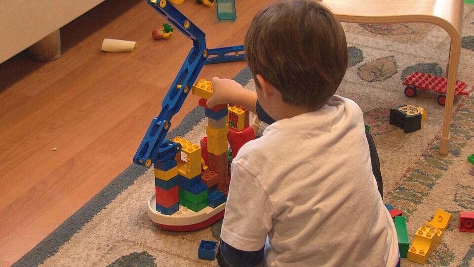 Un petit garçon joue avec un jouet dans une garderie