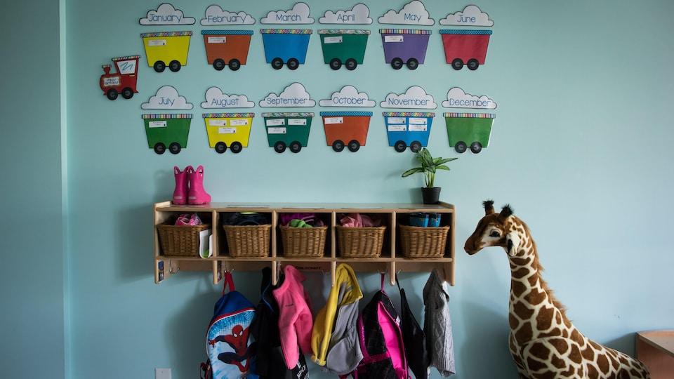 L'entrée d'une garderie, avec des casiers, des sacs à dos et une girafe en peluche.