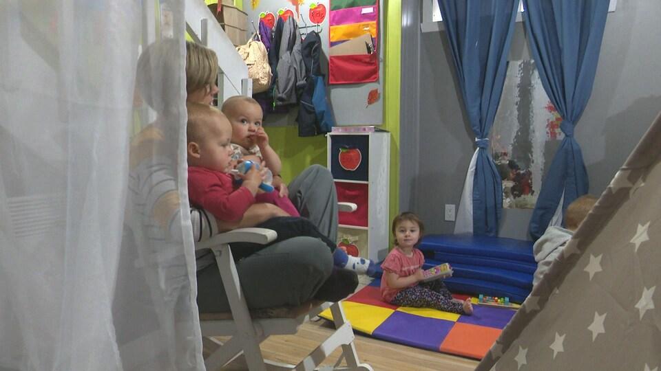 Josée Parisée berce deux bambins dans sa garderie familiale. Deux autres enfants jouent par terre dans la salle de jeux.