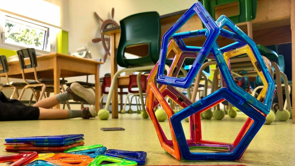 Des jeux posés à terre dans une salle de classe. En arrière-plan on aperçoit les jambes d'un enfant qui joue par terre.