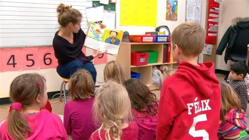 Des enfants écoutent une éducatrice.