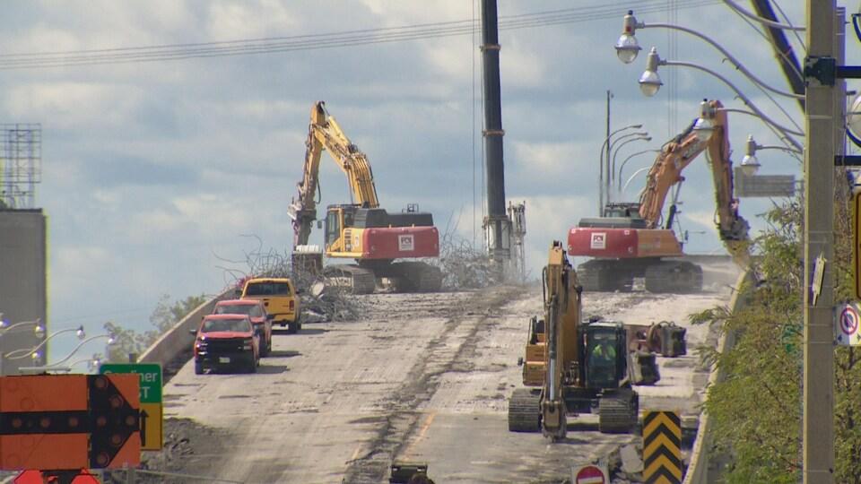Des équipements lourds et des camions travaillent sur une rampe d'accès en partie détruite.