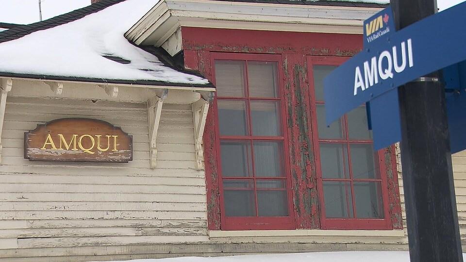 Plan rapproché d'une fenêtre de la gare d'Amqui dont la peinture rouge sur le cadre est à refaire
