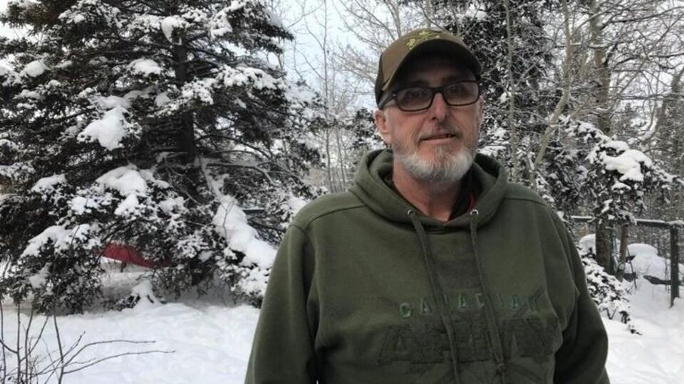 Gary Bath est debout devant des arbres enneigés.
