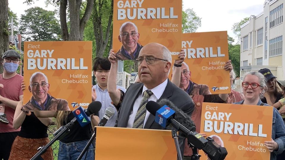 Un homme parle à une tribune, entouré de personnes qui brandissent des affiches électorales.