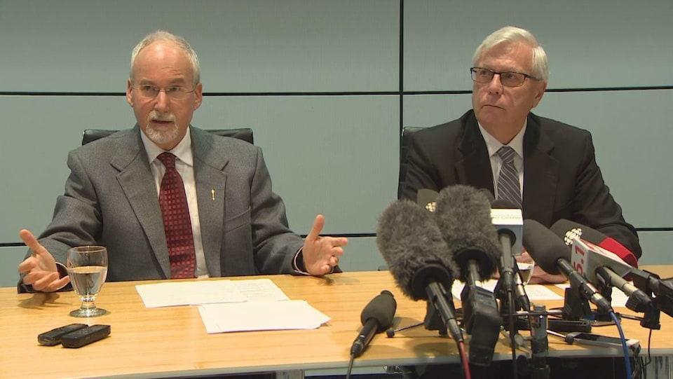Deux hommes assis à un bureau devant des micros.