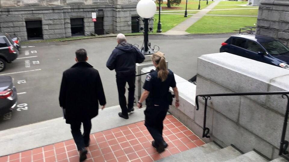 Gary Lenz descend un escalier, suivi par une agente de la GRC et un homme habillé en civil.