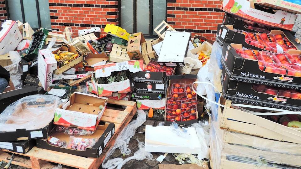 Des contenants de fruits sont empilés derrière un bâtiment.