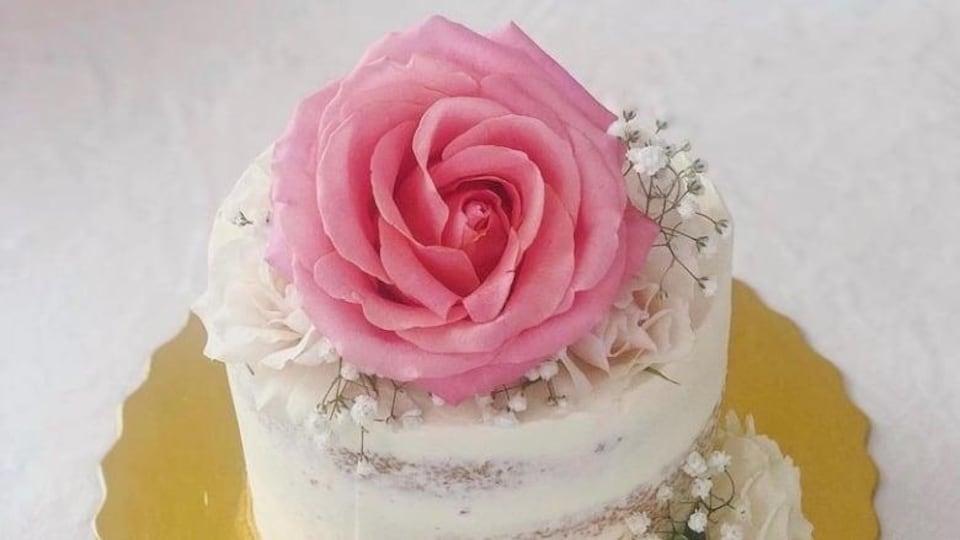 Un gâteau de mariage surmontée d'une crème en forme de fleur.