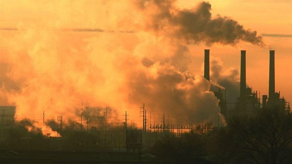 Trois citernes qui dégagent des nuages de fumée.