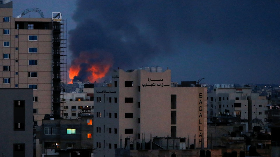 Des flammes et de la fumée derrières des immeubles.