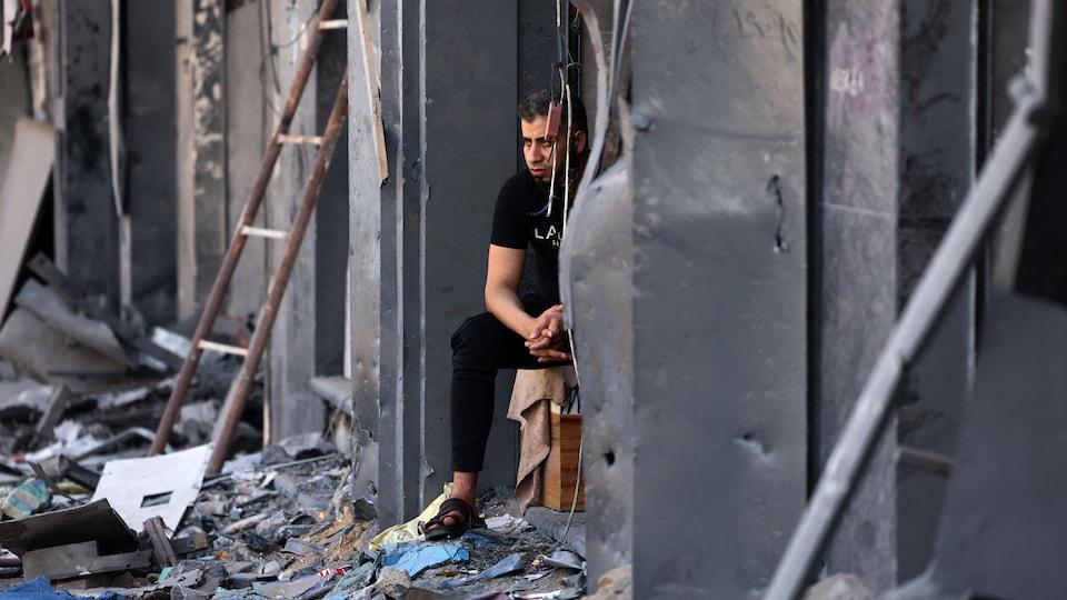 Un homme assis au milieu des ruines de son magasin à Gaza.