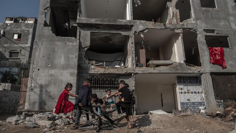Des enfants jouant dans des débris devant un immeuble détruit.