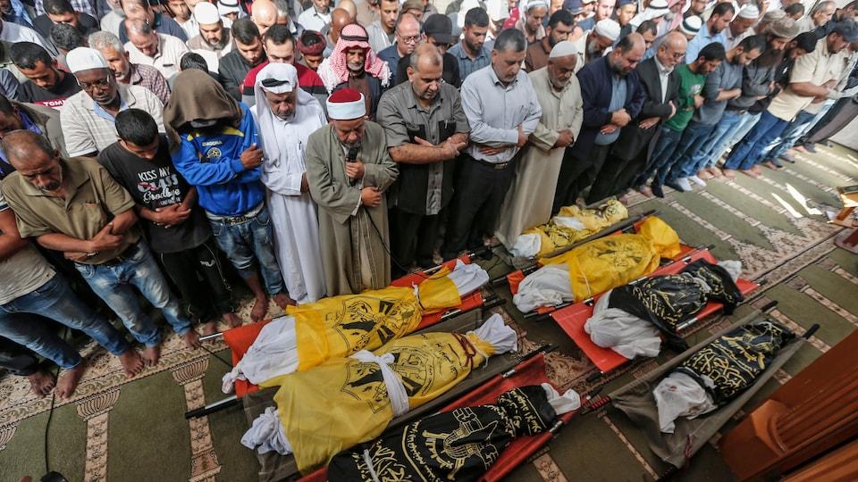 Des hommes prient devant les dépouilles de sept personnes.