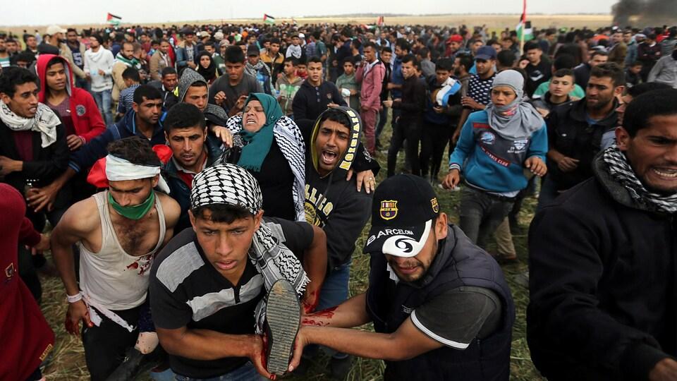 Une Palestinienne blessée est emportée par un groupe d'hommes à travers la foule.