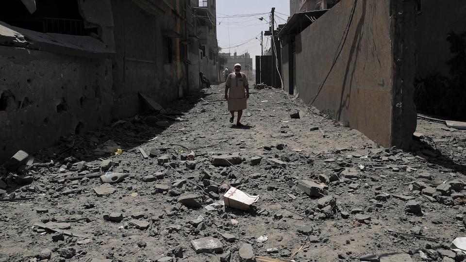 Un homme marche au milieu d'une rue dont le sol est jonché de débris.