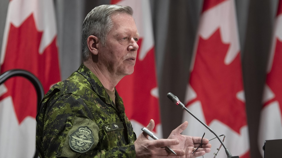 Jonathan Vance debout en uniforme de l'armée parle dans un micro.