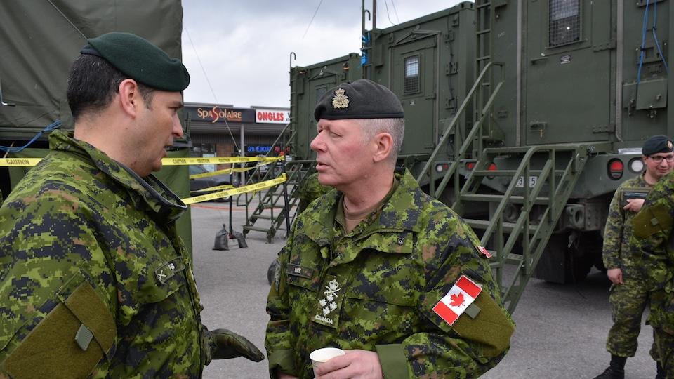 Le chef de l'état-major canadien, le général Jonathan Vance (à droite), discute avec un officier, à Pierrefonds.
