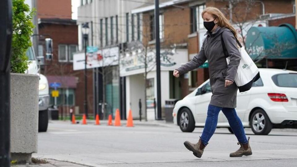 Une femme marche, sac à l'épaule, masque au visage.