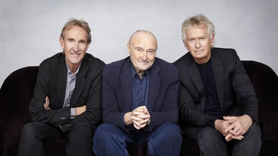 Les trois hommes posent assis et sourient.