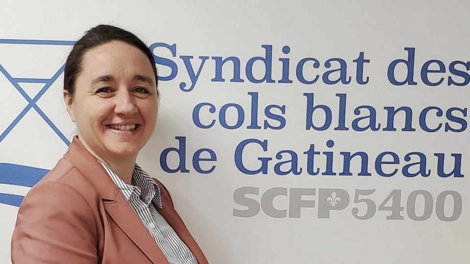 Geneviève Carrier devant une affiche du Syndicat des cols blancs de la Ville de Gatineau.