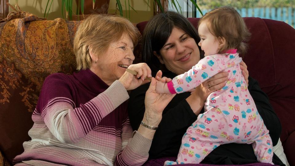 Une dame plus âgé sourit à un poupon tenu par sa maman.