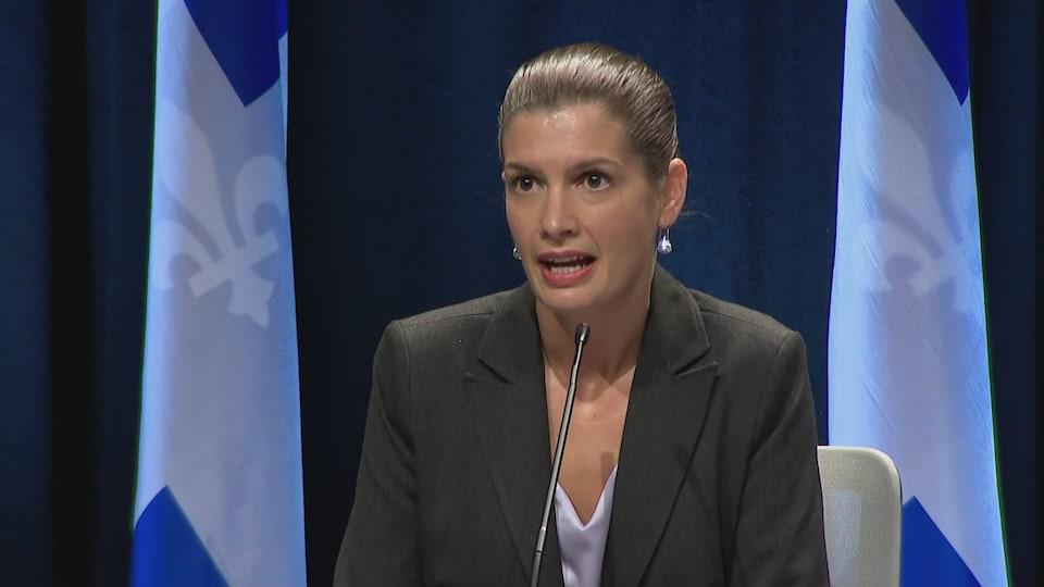 Geneviève Guilbault est assise devant des drapeaux du Québec.
